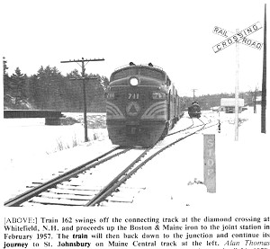 Black and White train in snow at railroad crossing