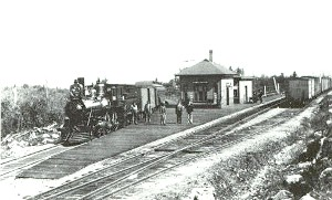 Black and White photo of steam engine train at small one room train station