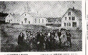 Early black and white photo of school with teacher ans students standing in front of three white buildings