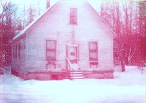 small white house in snow with reddish pink tint