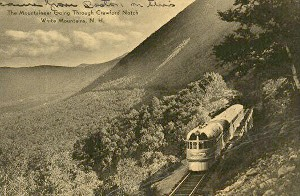 Sepia  toned photo of old style train climbing through forest on side of a mountain