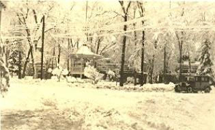 Black and white photo of elevated gazebo in the town center in winter. there are old 1900's cars parked around the green.