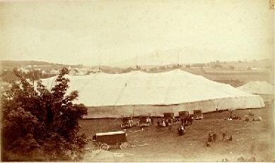 Big tent with earliest cars parked in front