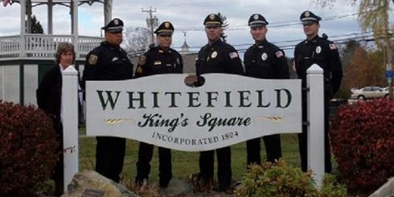Police Officers standing Behind Whitefield Town SigS
