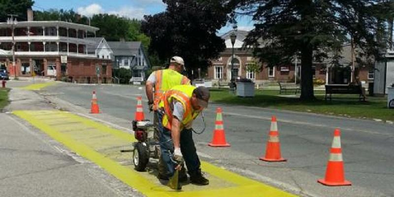 Two Construction Workers Painting Sidewalk